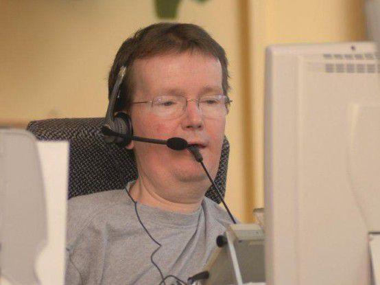 Der abgebildete Mitarbeiter ist Programmierer. Er ist auf einen Elektrofahrstuhl angewiesen und bedient die Tastatur per Mundstab.