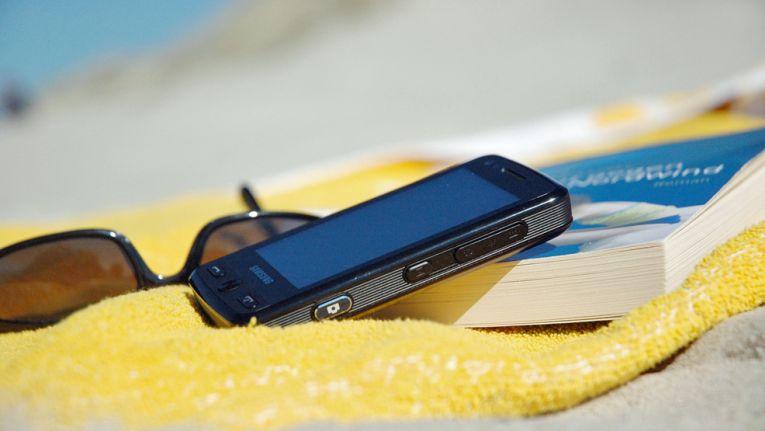 Oft ein teures Vergnügen: Das Smartphone muss überall mit - auch in den Urlaub.