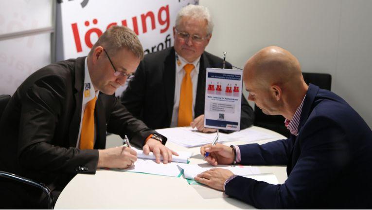 Arnd Villwock (ganz links) und Hermann Mertens (in der Mitte, beide Geschäftsleitung cop software + services) unterzeichnen mit Sven Glatter (ganz rechts), Geschäftsführer comTeam, auf der CeBIT die Vereinbarungen zur Zusammenarbeit.