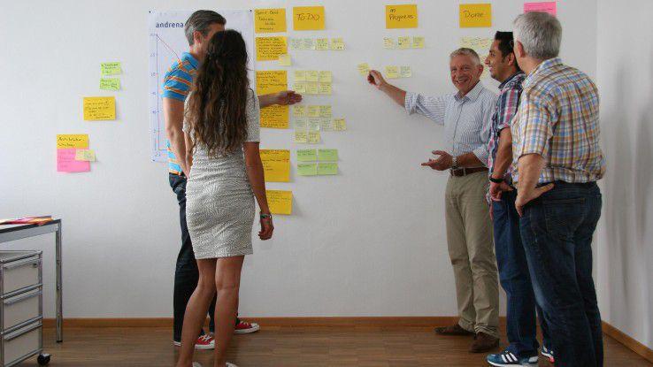 Martin Giebel (vorne rechts), Agile Coach bei Andrena, bespricht mit seinen Kollegen an der Pinnwand den Stand eines Projekts.