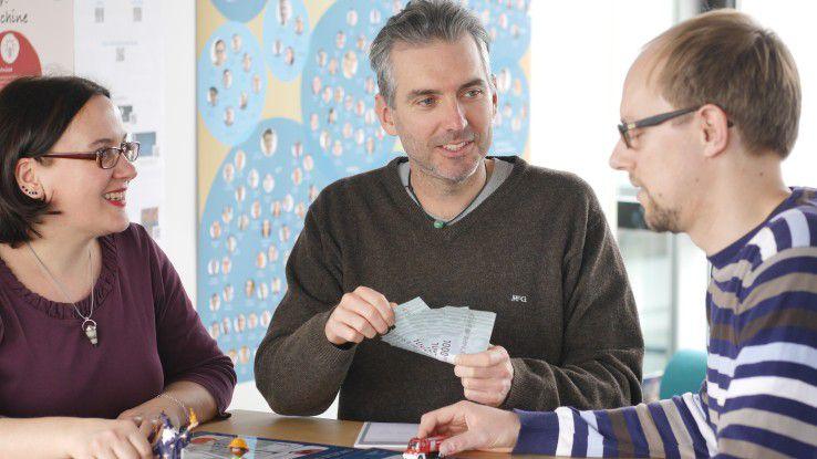 Blockchain-Experte Dirk Röder von MaibornWolff (Mitte) hat ein Kartenspiel entwickelt, um Kunden die Technologie verständlich zu machen.