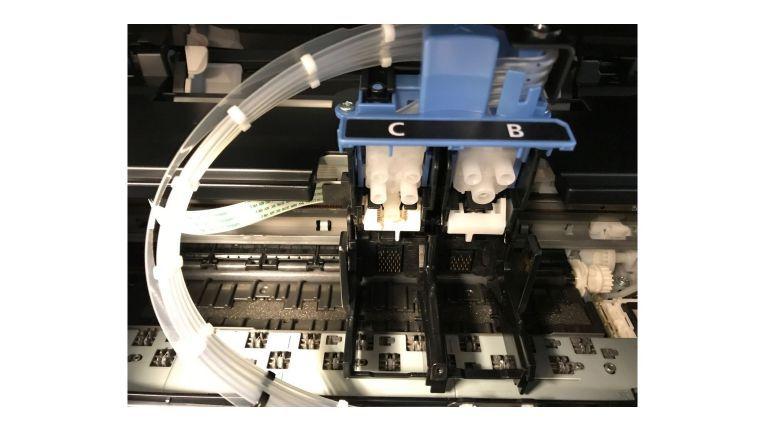 Bei der Inbetriebnahme des Canon Pixma G4500 stecken Sie die Druckköpfe für Farbe und Schwarz in die Stationen.