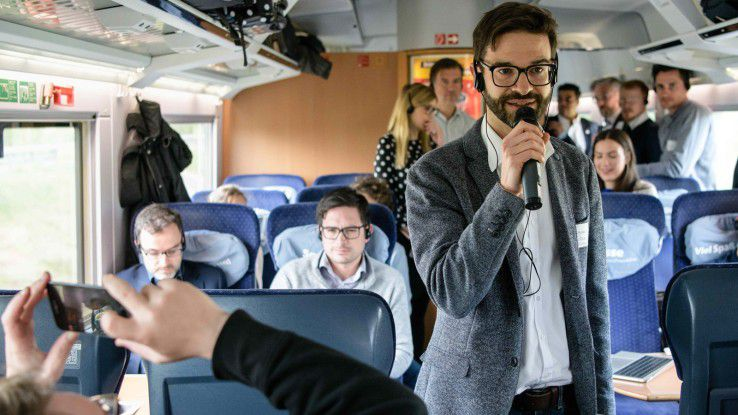 """Prof. Dr. Wolfgang Gruel stellte auf dem Weg von München bis nach Berlin den Zuggästen des """"Train2Republica"""" Fragen zu ihrem eigenen Mobilitätsverhalten."""