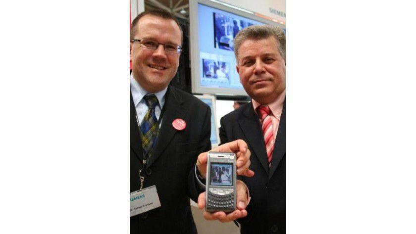Leitstelle für die Hosentasche: Dr. Andreas Brielmaier (Siemens, l.) und Ralf Schwirzheim (Syntron) zeigen auf der CeBIT Ihre kompakte Video-Überwachungs Lösung. Foto: Syntron/Siemens