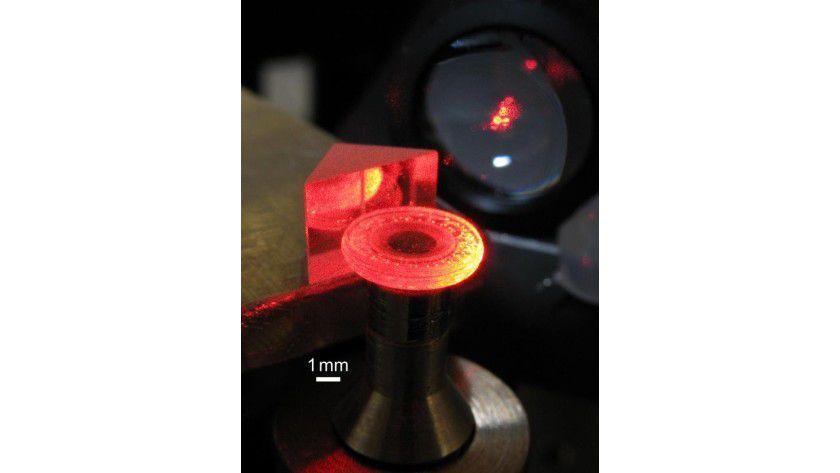 Käfig für Licht: Die leuchtende runde Scheibe ist ein Resonator, gefertigt aus einem Lithiumniobat-Kristall. Mit einem Prisma wird Licht eingekoppelt. Es ist in dem Resonator wie in einem Käfig gefangen, bis es durch Streuung entweicht. Zuvor hat es aber tausend oder mehr Umläufe in dem Kristall zurückgelegt. (c) Daniel Haertle, Universität Bonn, Bilderwerk