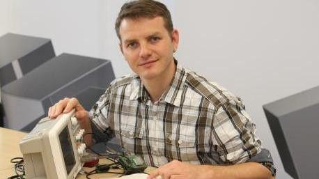 Mirko Lange misst mit einem Oszilloskop die elektrische Spannung von einem Teil einer Telematik-Box.