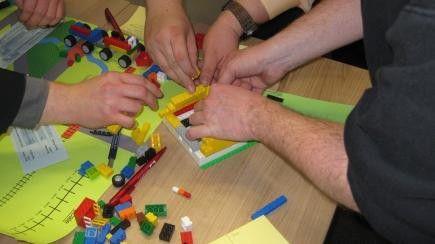 Macht Spaß und motiviert: Arbeiten mit Legosteinen während einer Scrum-Schulung.