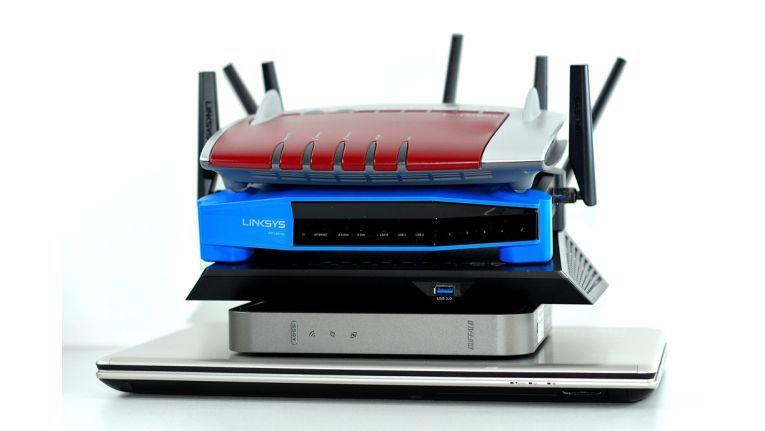 Vier Gigabit-WLAN-Router auf einem 4K-Laptop von Toshiba: AVM Fritzbox 7490, Linksys WRT1900AC, Netgear Nighthawk AC1900 und die Buffalo Airstation 1300.