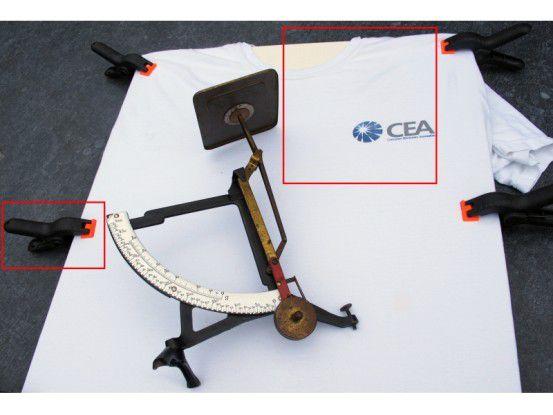 Ein Brett, mit einem T-Shirt bespannt, das mit ein paar Klammern glatt gezogen wird, ergibt einen reflexionsarmen Untergrund für die Objektfotografie.