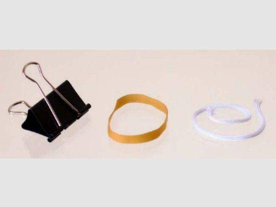 Einfachste Mittel: Mit einer Vielzweckklemme (Foldback-Klammer), Gummiband und Nylonseil ist eine universelle Smartphone-Halterung schnell und sauber zusammengebaut.