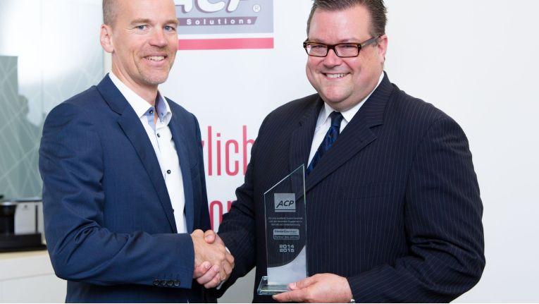 """Christoph Harvey, Vorstand der DeskCenter Solutions AG (rechts), überreicht bei der offiziellen Übergabe in Wien Rainer Kalkbrener, CEO der ACP Gruppe, die Auszeichnung """"Partner des Jahres 2014""""."""