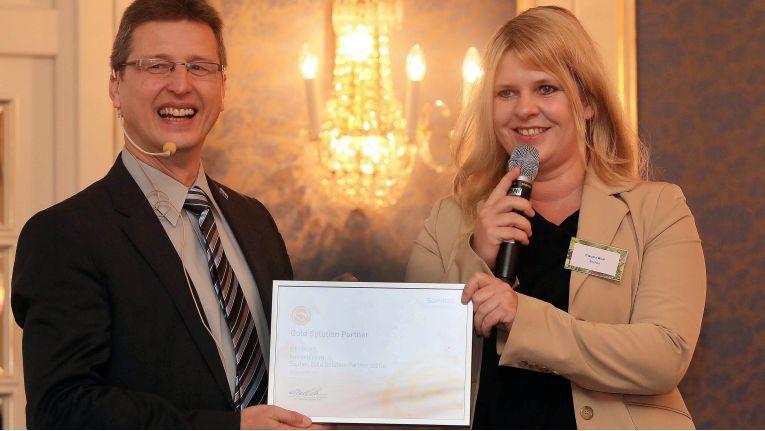 Claudia Wolf von der Sophos GmbH überreicht Rolf Braun, COO Cema AG, die Urkunde zum Gold-Partner-Status.