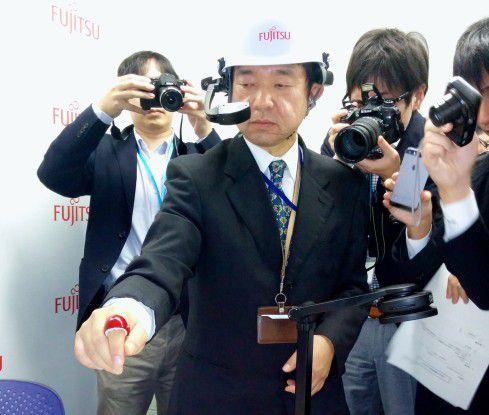 Yuichi Murase, Forscher in Fujitsus Human Centric Computing Laboratories präsentiert Ring und Spezialhandschuh.