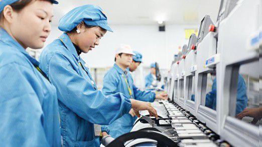 Mitarbeiter arbeiten vor den automatischen Bestückungslinien bei Hella Shanghai Electronics. Jährlich verlassen über 35 Millionen bestückte Leiterplatten die Produktionshallen des Werkes. Insgesamt arbeiten 1143 Beschäftigte in diesem Werk, wo Bauteile der Licht- und Karosserieelektronik sowie Sensoren und Komponenten hergestellt werden.