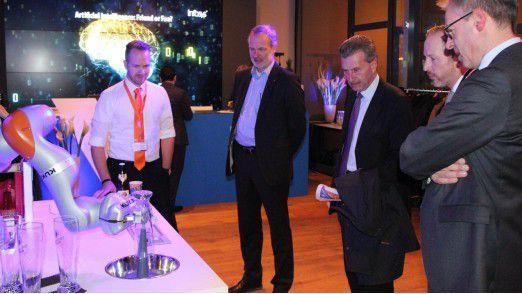 EU-Kommissar Günther H. Oettinger (3. von links) lässt sich den Kuka-Roboter vorführen, der ein Weißbier einschenkt.