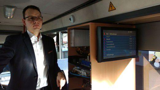 CIO Frank Scholz von DB Regio steht im mobilen Labor und zeigt, welche Technik bald in S-Bahnen funktioniert.