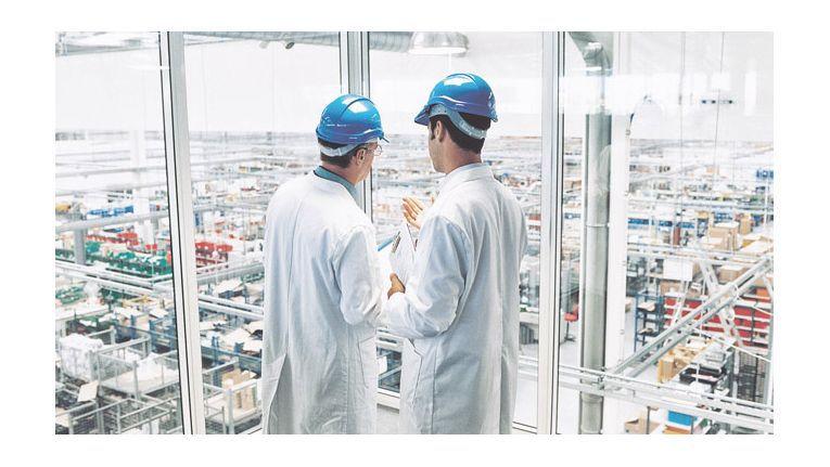 Mitarbeiter überwachen die Fertigung in einer Produktionshalle.