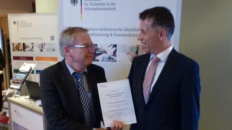 Bernd Kowalski, Abteilungsleiter im BSI, und Markus Schwind, Senior Vice President, Head of Sales Atos GBU Germany, bei der Übergabe der Registrierungsunterlagen auf dem Omnisecure-Kongress in Berlin.
