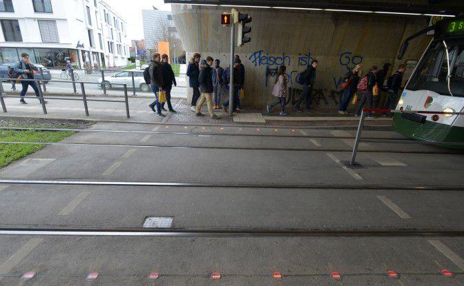 Test der Stadtwerke: Blinkende LED-Leuchten im Boden sollen Smartphone-Nutzer auf das Rotlicht der Ampel am Fußgängerüberweg hinweisen.