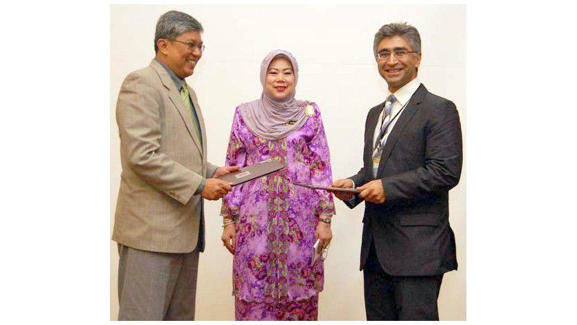 Prof. Dr. Mohamed Ridza Wahiddin (links) und Prof. Dr. Ahmad-Reza Sadeghi (rechts) tauschen die Dokumente aus, in der Mitte Madinah Mohamad vom Malaysischen Wissenschaftsministerium. Foto: RUB