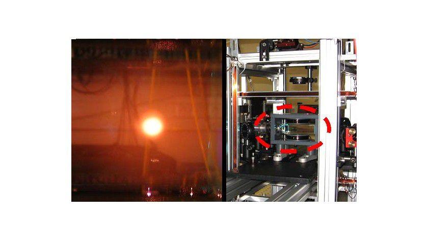 Linkes Bild: Lasergekühlte Metalldampfwolke aus Rubidiumatomen (orange), die im Inneren einer Vakuum-Glaszelle erzeugt wird und eine Temperatur nahe des absoluten Nullpunktes (-273 °C) hat. Rechtes Bild: Glaszelle (roter Kreis) mit Spiegeln und Linsen für die Laserstrahlen und Magnetspulen aus Kupferdraht zur Abschirmung vor elektromagnetischen Streufeldern. Fotos: Uni Heidelberg