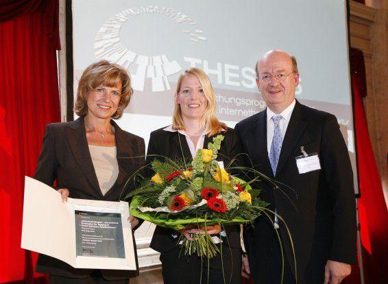 Sonja Kraus nimmt von Professor Wolfgang Wahlster und Wirtschaftsstaats-<br/>sekret&auml;rin Dagmar W&ouml;hrl den mit 10.000 Euro dotierten Preis entgegen.