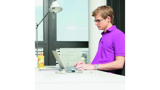Ein Angestellter mit dem eigenen Notebook im Büro.